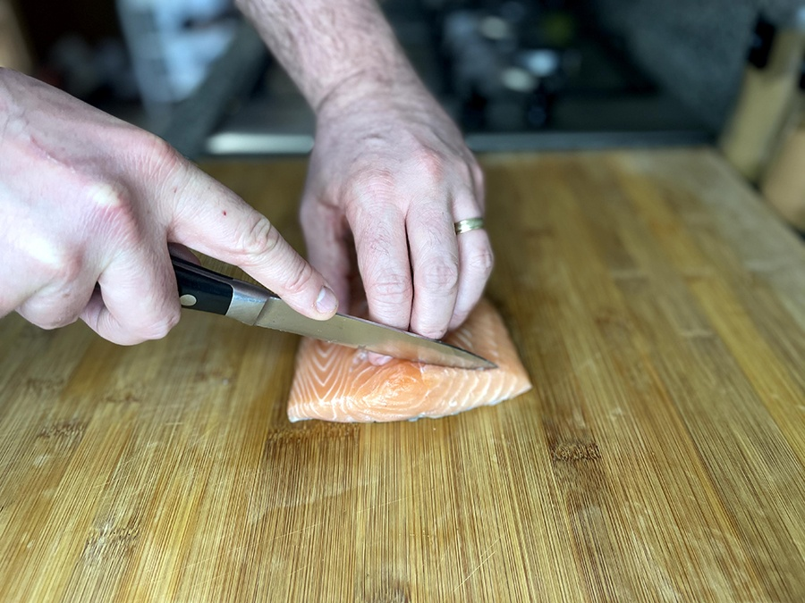 A chef cutting some salmon on a chopping board