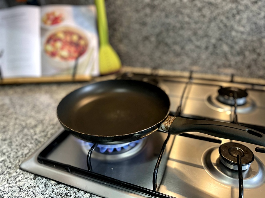 an old non-stick frying pan on a gas hob