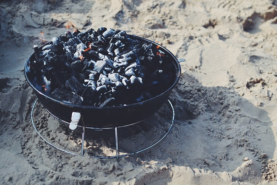 A charcoal grill on sand